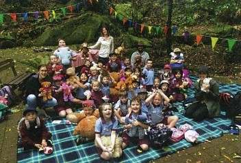 27 kindergarten students sitting on picnic rugs on a paved clearing in the rainforest holding their teddies and smiling