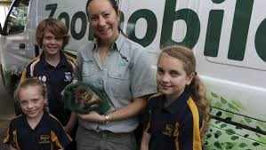 three young children standing in front of Zoomobile van with Zoo officer holding a ring tailed possum in a knitted bag