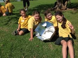 four students with solar oven